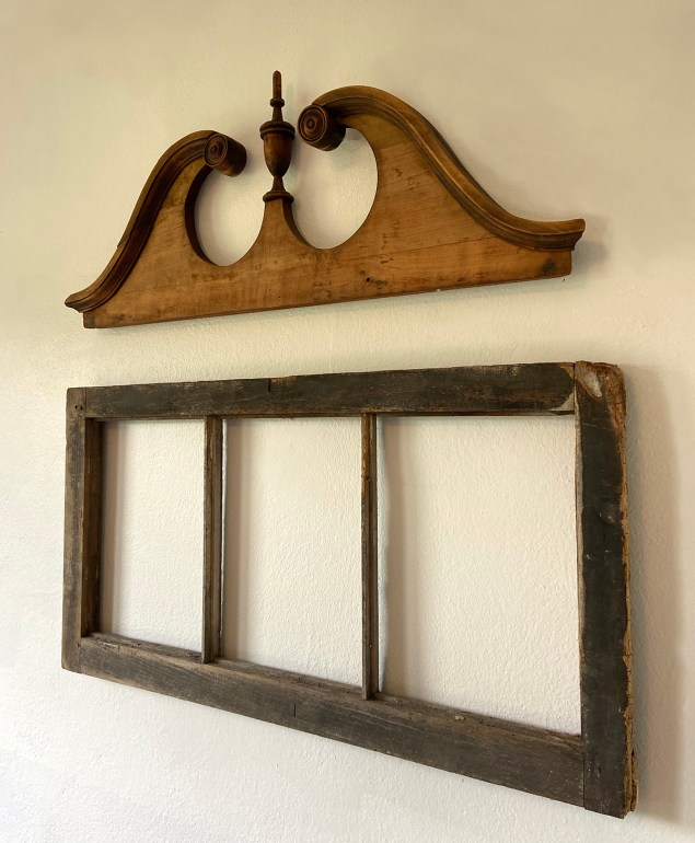 salvaged furniture pediment hung on a wall as decor