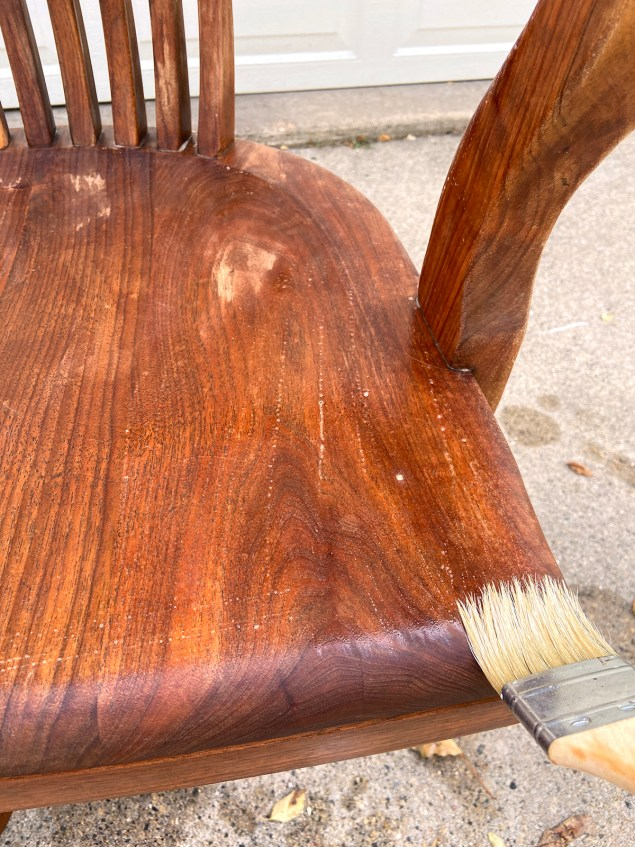 spreading bleach onto the chair with a paintbrush
