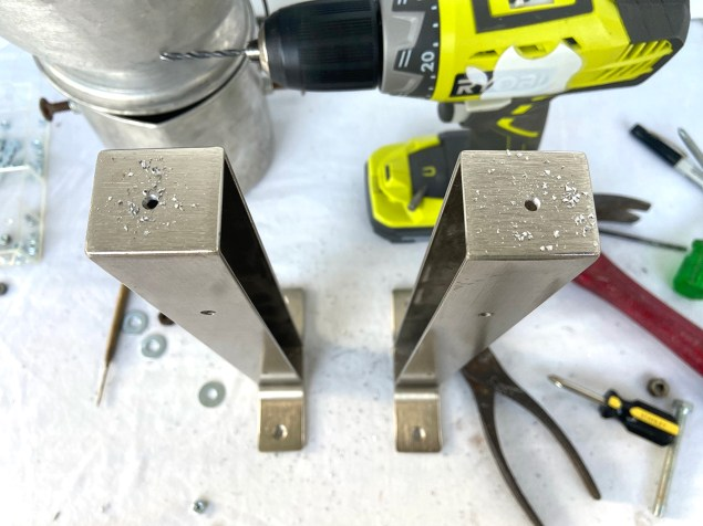 Drilling holes into the Ikea shelf brackets which will become Robot Frankenstein's legs