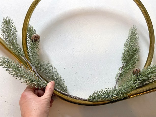 Adding greenery to a vintage brass horn to turn it into a wreath