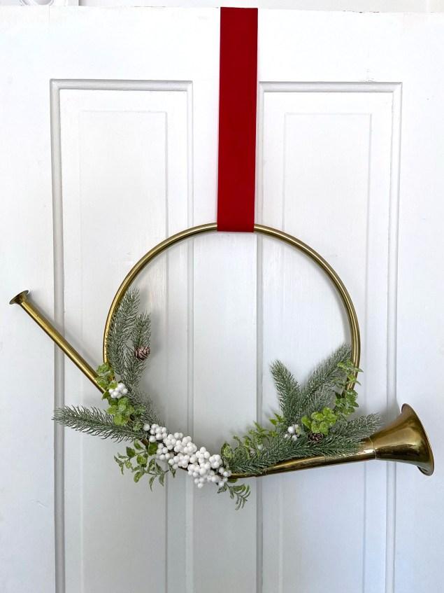 Brass French horn wreath hanging on door