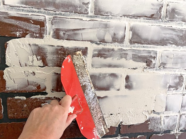 applying a German schmear of joint compound to a faux brick wall