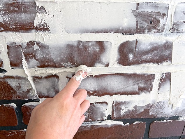 dragging a fingertip through the mortar line in the faux brick wall
