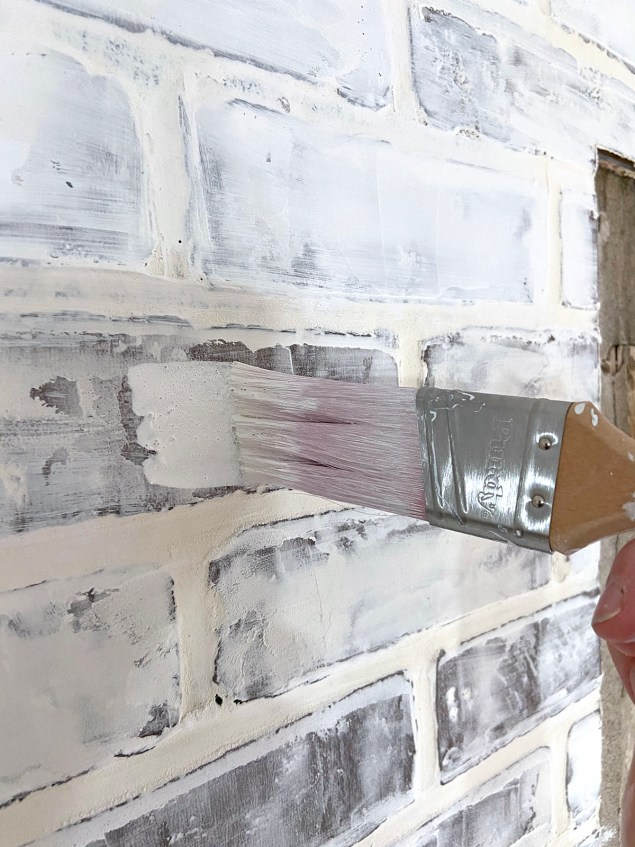 painting the faux brick wall with watered down paint