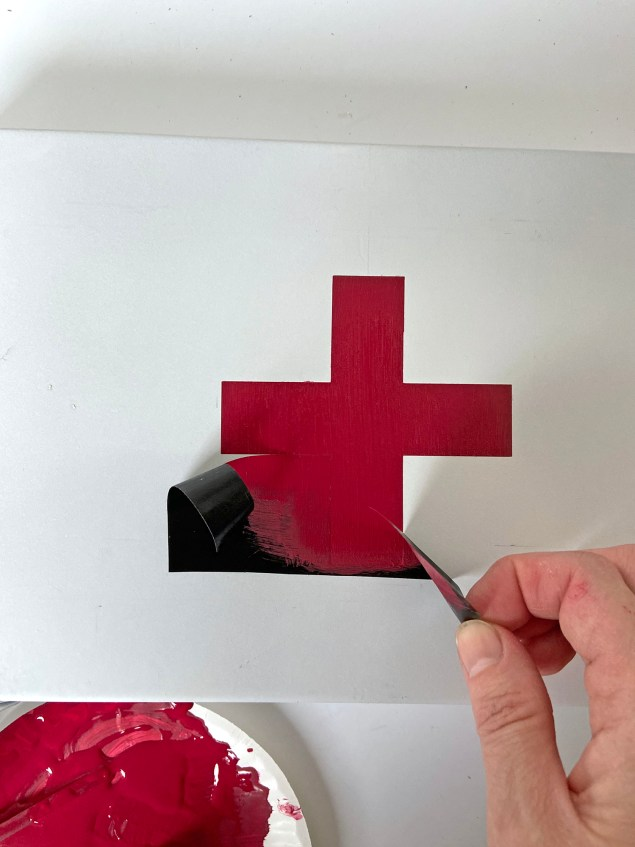 peeling the stencil up from the red cross