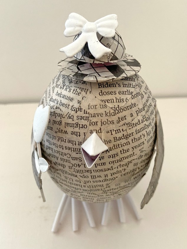 decoupaged newspaper chick with crossword puzzle hat