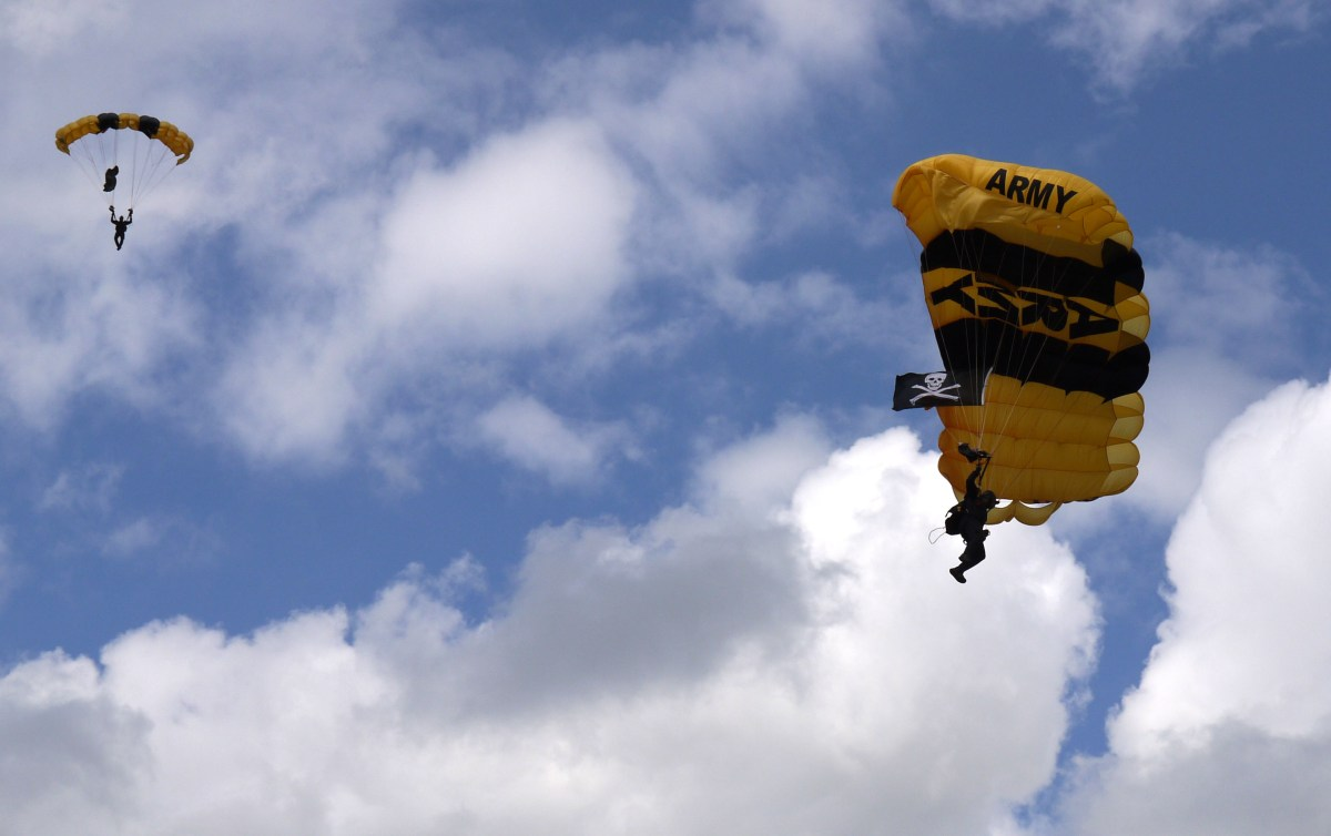 A member of the Army's Golden Knights parachute team spots his landing at the Middleton High School football field at a year-end pep assembly