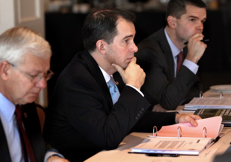 Gov. Scott Walker, then-chairman of the Wisconsin Economic Development Corp., participates in a WEDC board meeting in late 2013 in La Crosse along with CEO Reed Hall, left, and then-chief operating officer Ryan Murray. Walker removed himself in July as chairman of the board after a negative audit and critical news coverage of the job-creation agency. Murray has left the agency, and Hall will retire in September. Hall's replacement is longtime banker Mark Hogan.