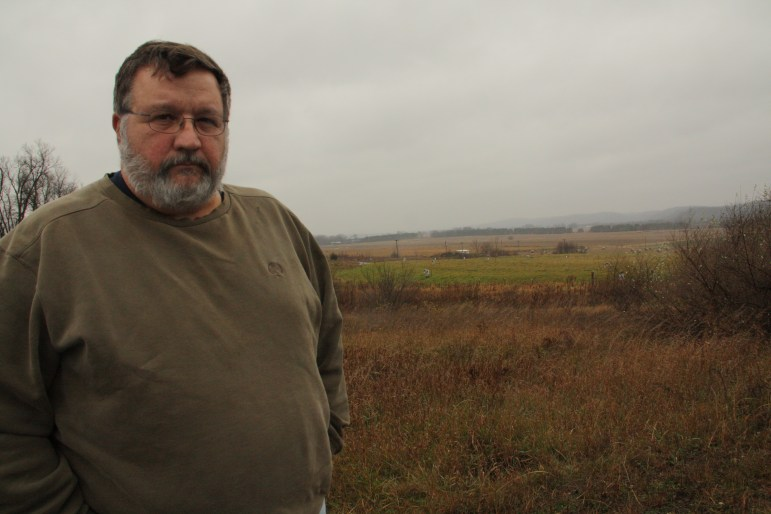 Mike Sitton, commander's representative for the Badger Army Ammunition Plant, said the cost of environmental cleanup so far at the site has been around $125 million. In the background is the old propellant burning ground where contaminated soil and groundwater were treated and the site capped in 2008.