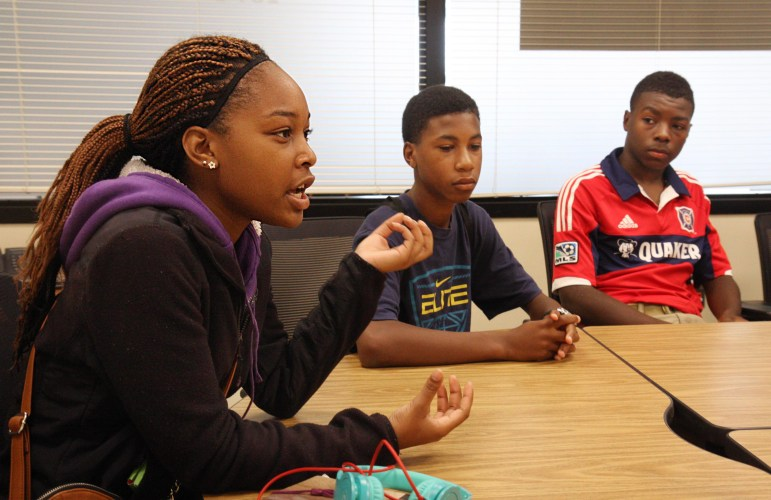 Sophomores William Lemkuil, center, and Demitrius Kigeya, right, listen to Danaejuh Sheppard during a roundtable discussion with other students from Madison Memorial High School's Black Student Union in August. Sheppard, a senior, discusses a proposed mentoring program at the high school that would partner younger students with older students.