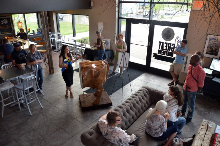 """WCIJ multimedia director Kate Golden explains the significance of the cow-shaped art piece """"A Day in Brown County"""" to an audience at Great Northern Distilling in Plover, Wisconsin on May 7, 2015. The exhibit was part of the """"Investigative Reporting + Art"""" tour put on by Carrie Roy and WCIJ."""