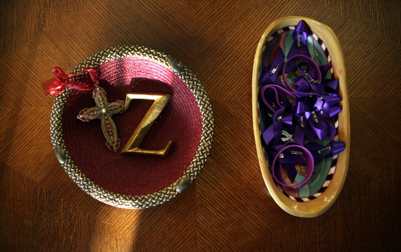 """Elvin and Cheryl Daniel keep a bowl on their coffee table with a cross, a """"Z,"""" and a basket of ribbons and bracelets in Zina Haughton's favorite color, purple, to remember Elvin's slain sister. Haughton was murdered by her estranged husband with a gun he purchased via Armslist.com, despite having a restraining order against him."""