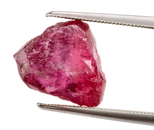 Rough red gemstone held in tweezers