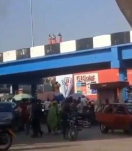 3 Young Men On Red Wrapper Caught Taking Their Bath On A Bridge In Ibadan (Video)