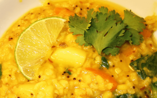 kitchari with lemon slice and cilantro in a white bowl