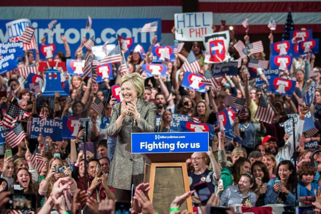 Hillary Clinton at rally in front of large crowd with signs
