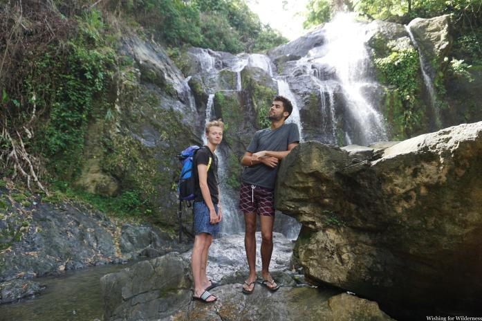 Two people pose by a waterfall