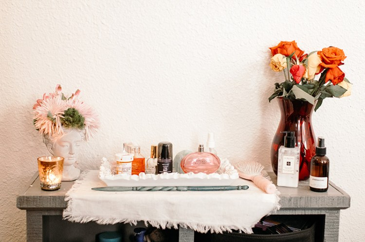 perfume and flowers on a shelf studio apartment wit & delight