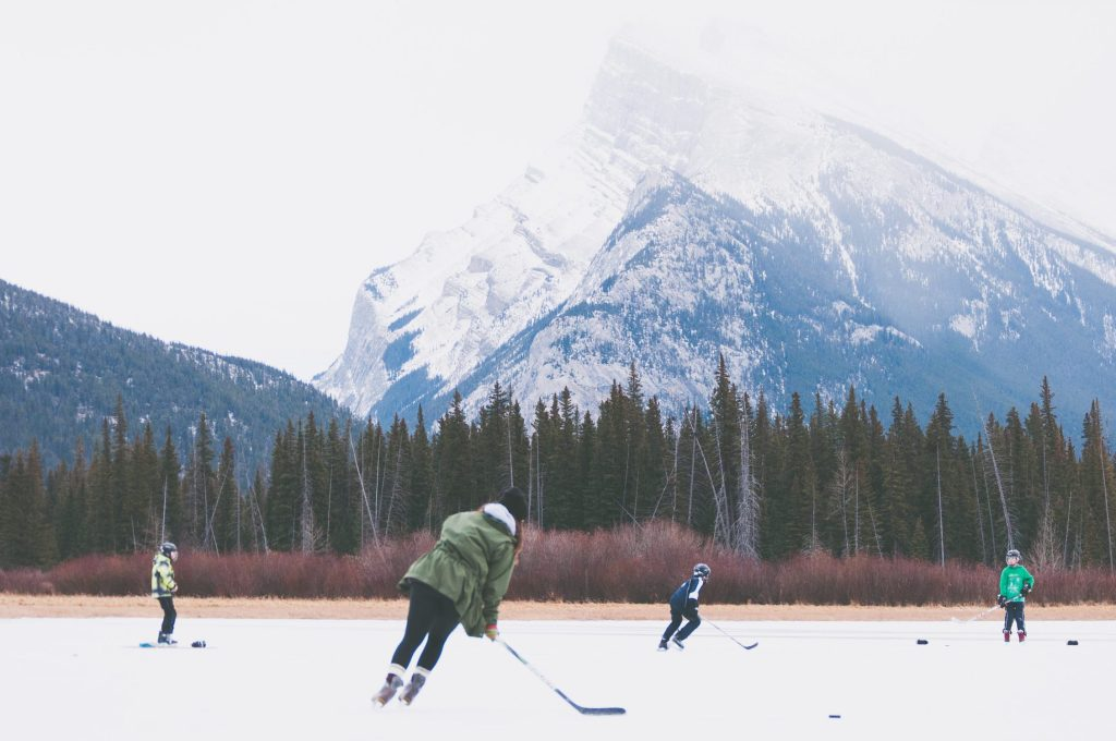 photo of people playing hockey in front of a mountain