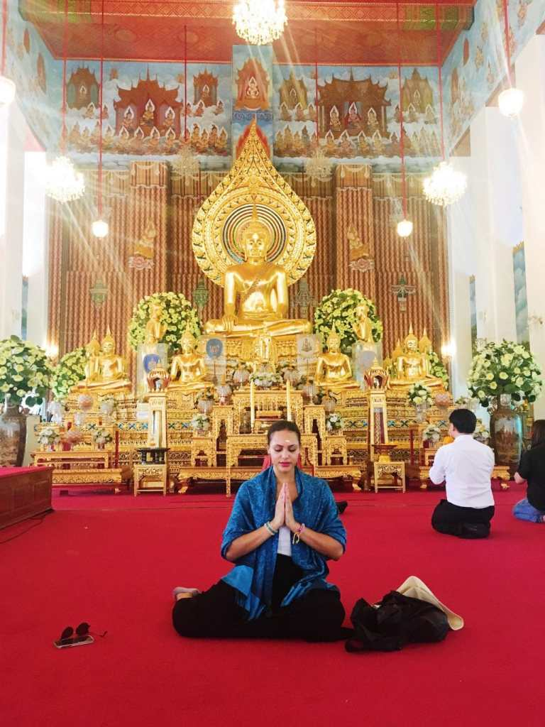 Temple interior of Wat Chana Songkram with many gold accents and Buddha statues.