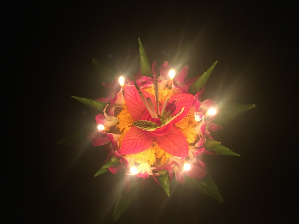 Flower boat glowing during Loy Krathong ceremony in Phang Nga Bay, Thailand.