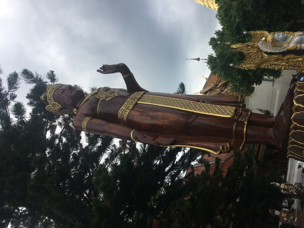 Brown and gold Buddha statue at Wat Doi Suthep in Chiang Mai, Thailand.