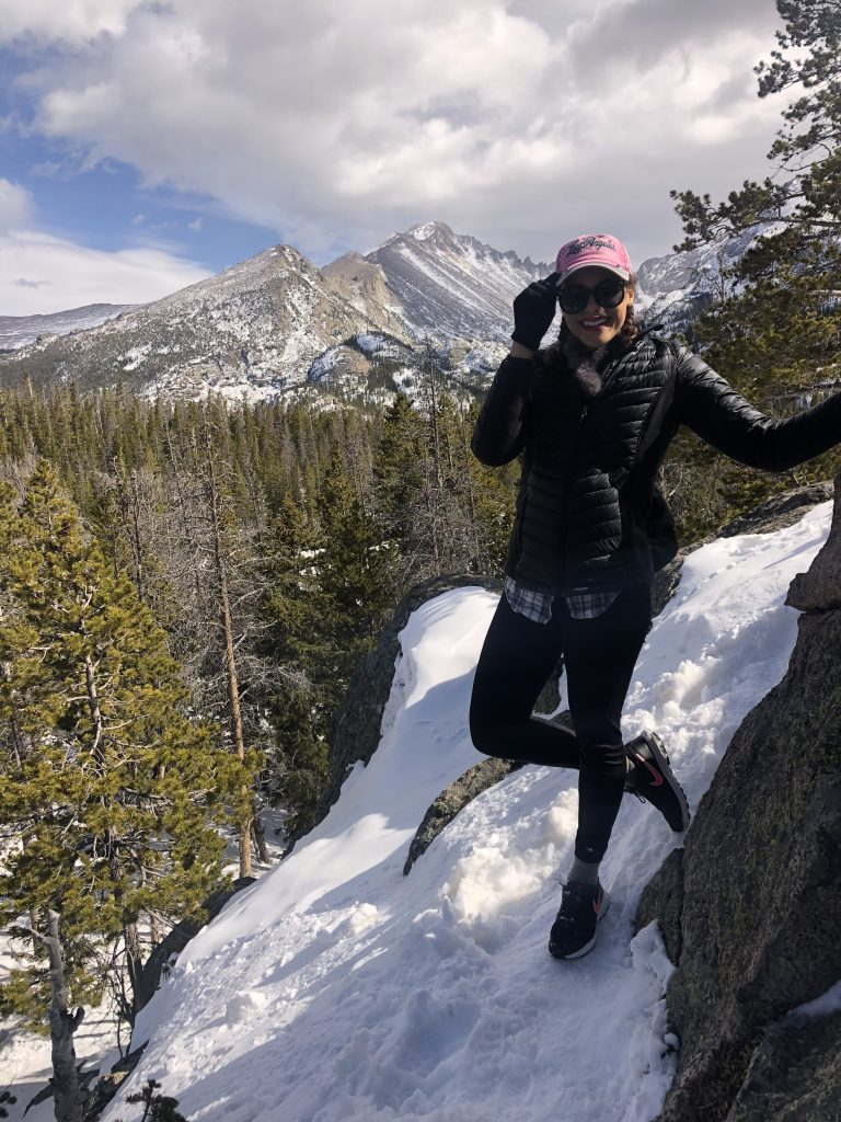 Photo of me on top of a snowy rock structure to get some mountain views in Rocky Mountain National Park