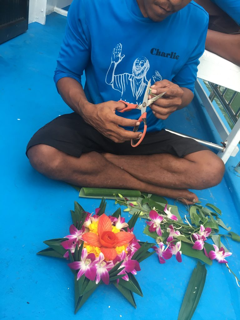 Kayak tour guide makes flower boat for Loy Krathong ceremony in Phang Nga Bay, Thailand.
