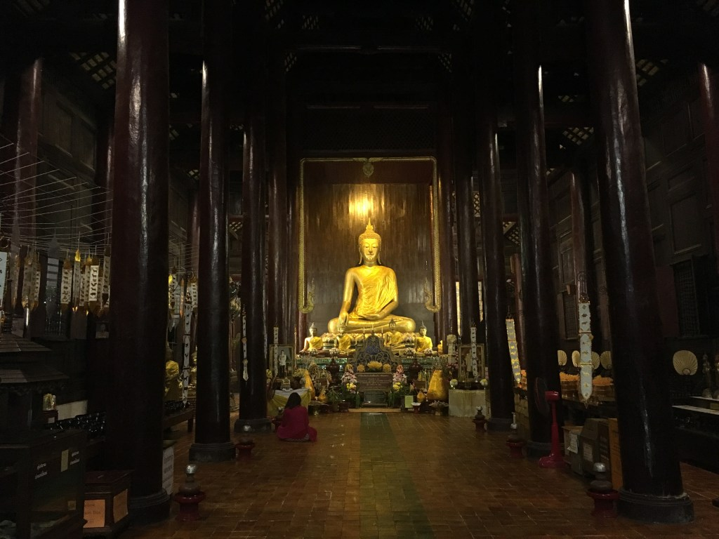Photo of shining gold Buddha statue inside temple at sunset Wat Phan Tao in Chiang Mai, Thailand