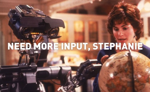 Johnny 5 and ally sheedy look at a globe, as johnny requests input.