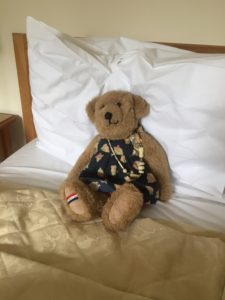 A hand-made teddy bear ('Jacquie Bear') sitting on a bed.