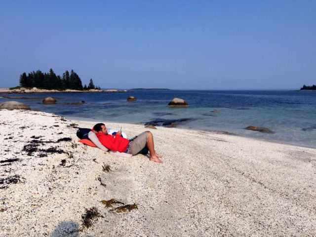 Reading on Wheat Island beach in Penobscot Bay