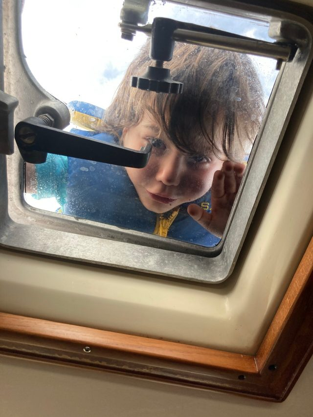 Boat kid! Toddler peeking through the hatch on our Sabre 42 sailboat