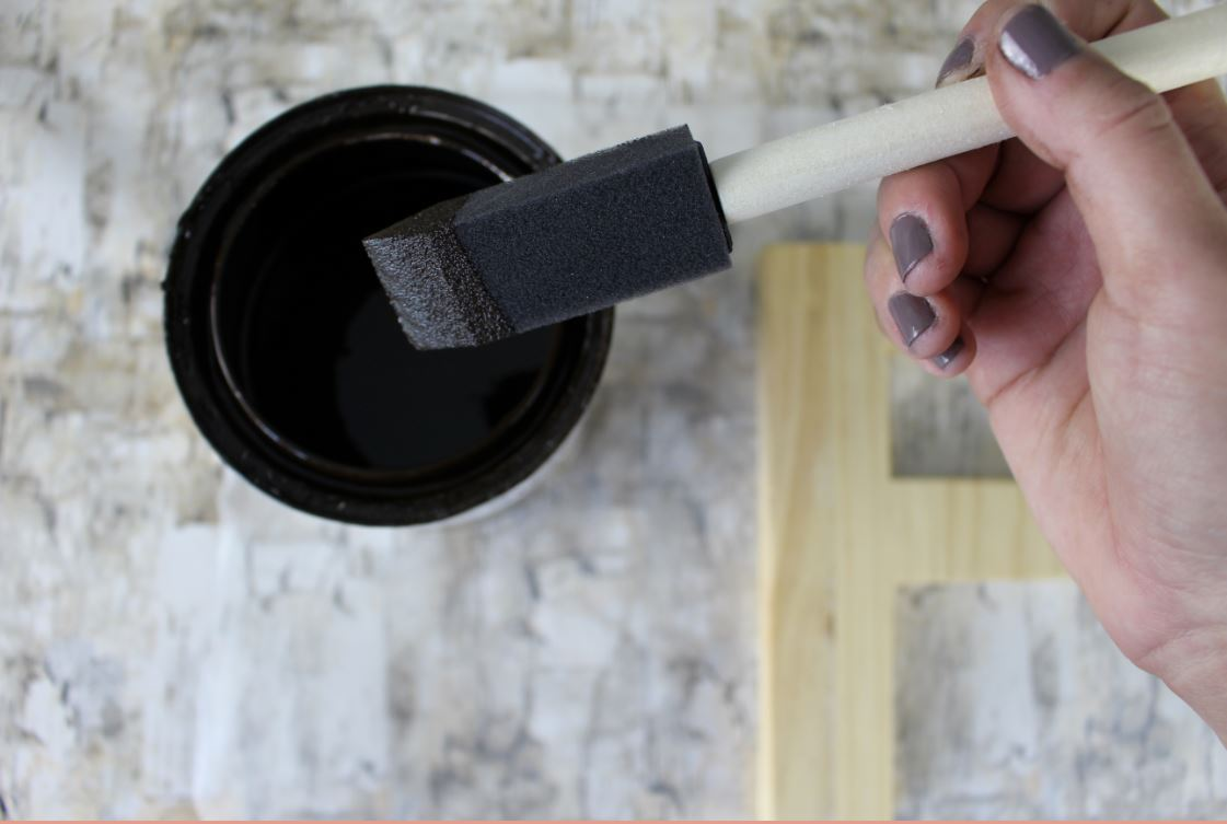 Using a foam brush to apply stain to wooden letter.