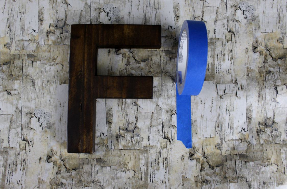 Using painter's tape to add detail to a wooden letter when painting.