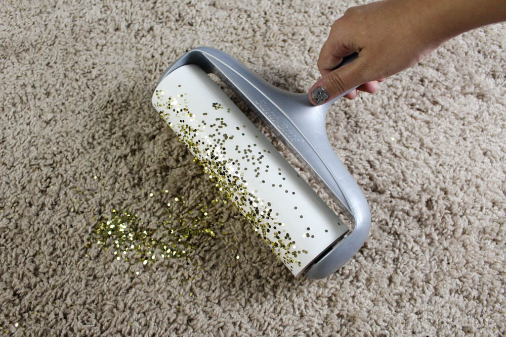 Getting glitter out of the carpet with Scotch-Brite lint roller.