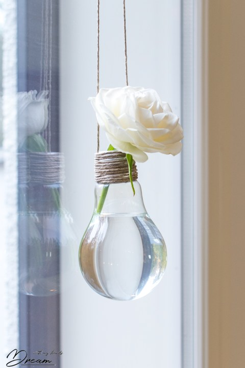 The hanging light bulb vase at the window.