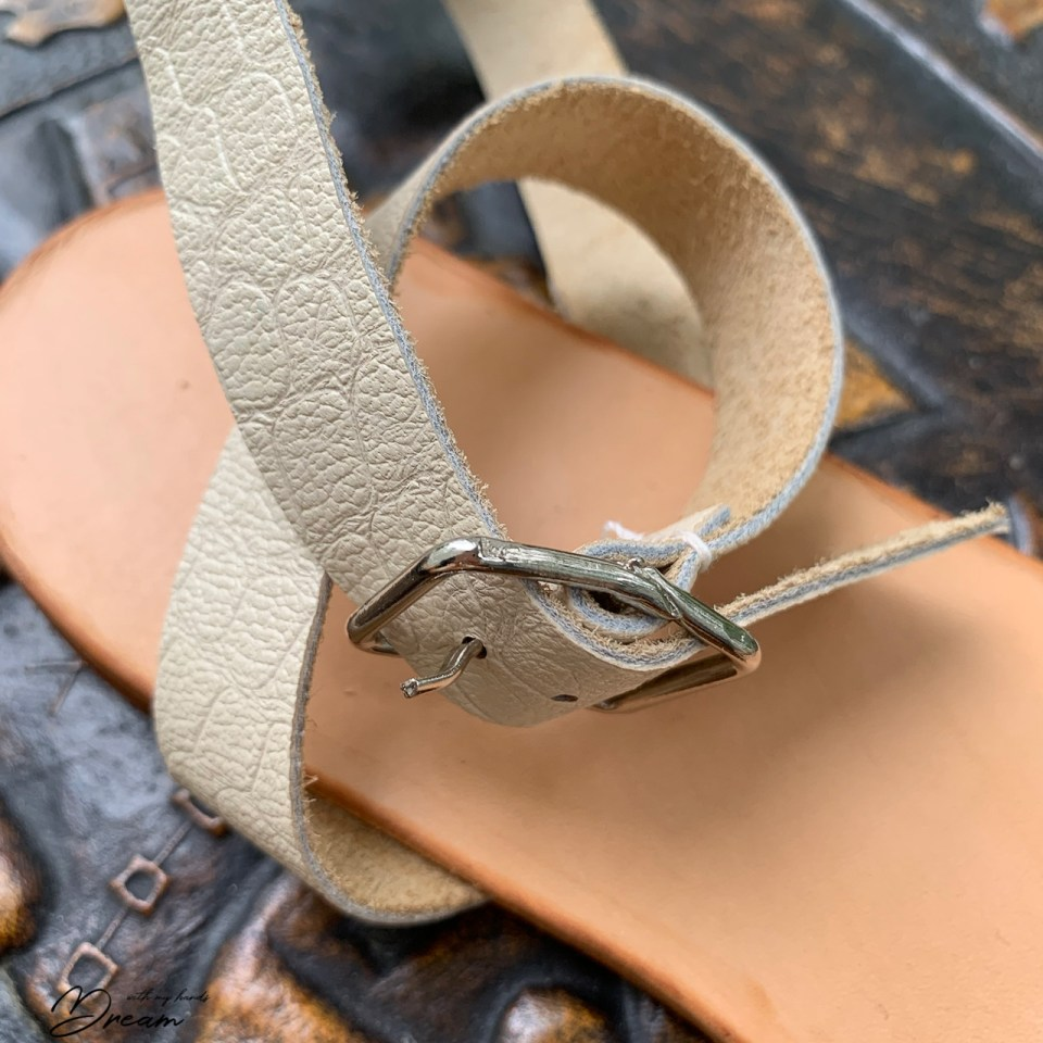 The detail of the sandal buckle fastening.