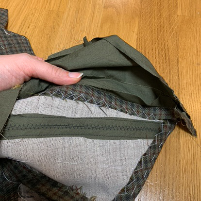 The waistcoat facing is cross-stitched to the canvas.