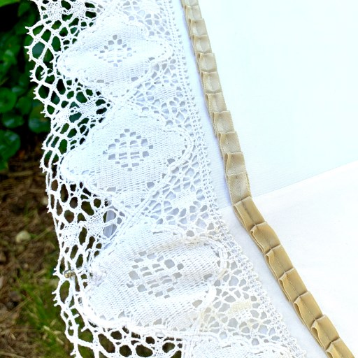 The lace edging and the pleated ribbon decoration.