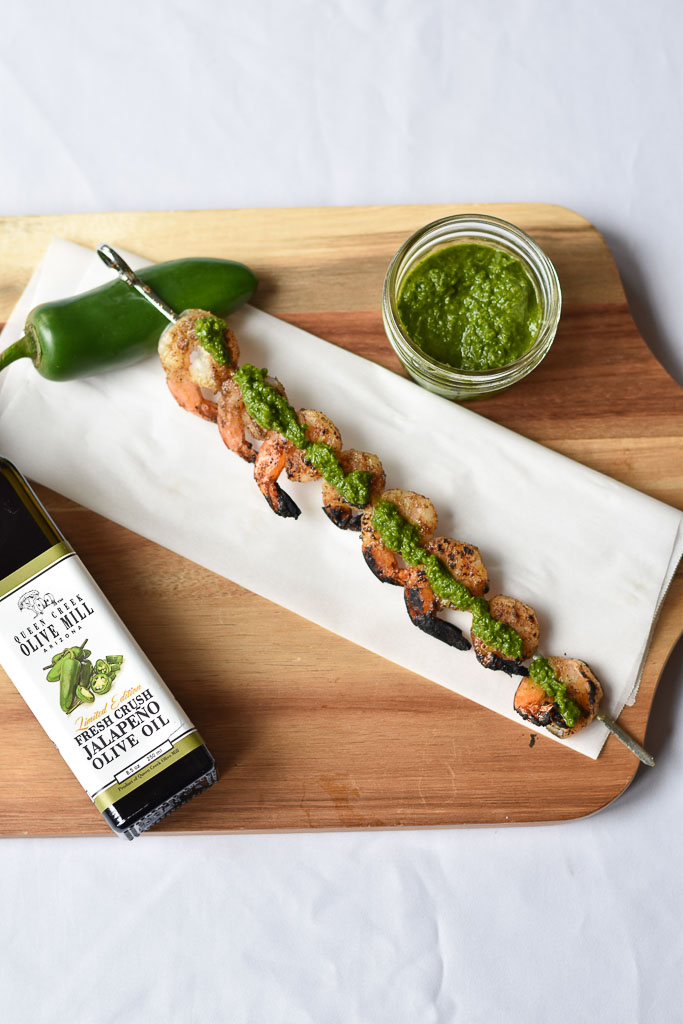 One Grilled Shrimp Skewer with Jalapeno Chimichurri on top of the shrimp.