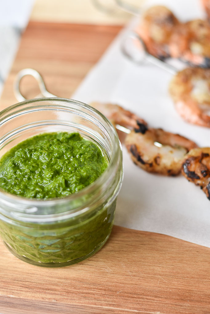 A jar of Jalapeno Chimichurri with grilled shrimp skewers in the background.