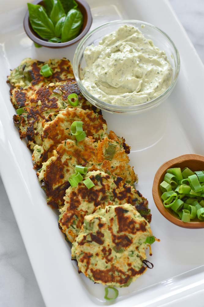 Carrot Zucchini Fritters on a platter with a side of Aioli