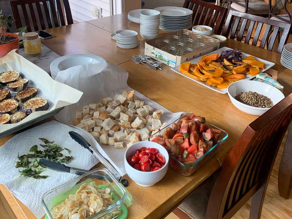 A table with many ingredients and dishes for the dinner party
