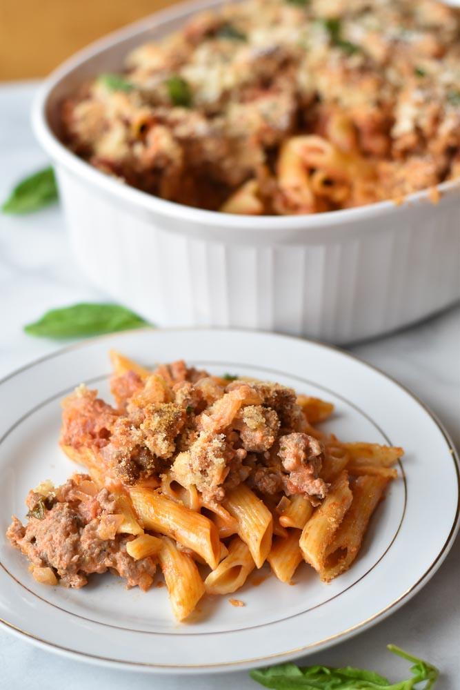 A plate and a casserole dish of creamy sausage pasta bake
