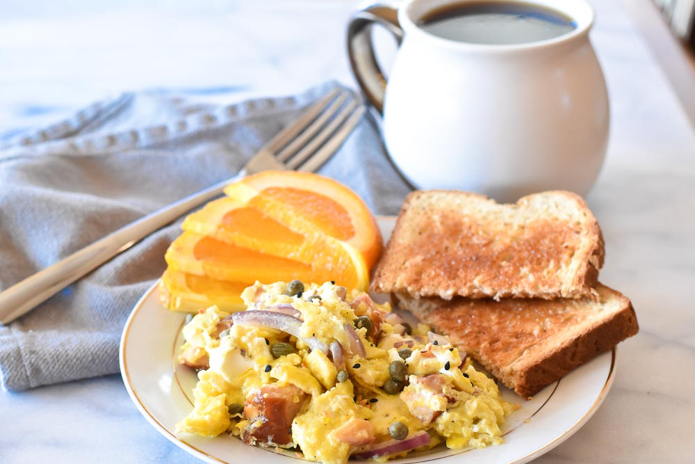 Salmon Breakfast Scramble on a plate with a fork and coffee