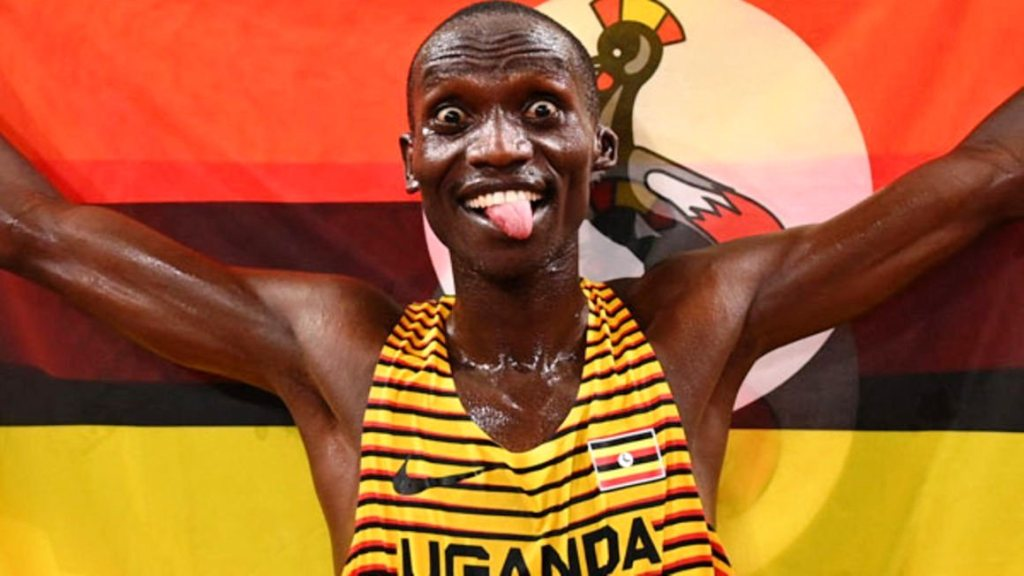 ganda's Joshua Cheptegei celebrates with the national flag after winning the men's 5000m final