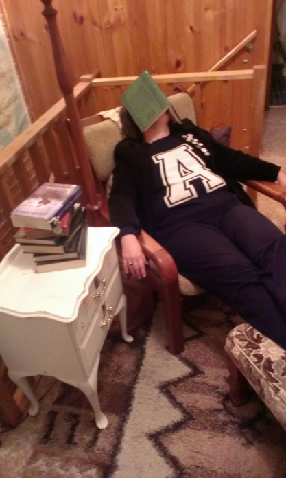 The Shopping Sherpa lying back on a chair with a book over her face