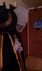A hat rack with a dragon decoration and a beanie in the shape of a knight's helmet, with a painting of more dragons in the background