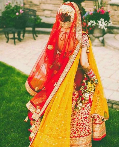red and gold lehenga with a yellow and red net duppata and gold gotta work all over